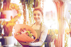 Smiling florist woman with bunch at flower shop Stock Photo