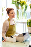 Smiling florist woman at flower shop cashbox Stock Image