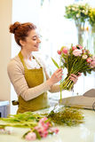 Smiling florist woman making bunch at flower shop Stock Images