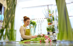 Smiling florist woman making bunch at flower shop Stock Photos