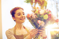 Smiling florist woman making bunch at flower shop Royalty Free Stock Photo