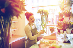 Smiling florist woman making bunch at flower shop Royalty Free Stock Photos