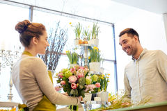 Smiling florist woman and man at flower shop. People, shopping, sale, floristry and consumerism concept - happy smiling florist women making bouquet for and men Royalty Free Stock Photos