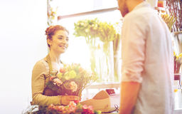 Smiling florist woman and man at flower shop Royalty Free Stock Photos