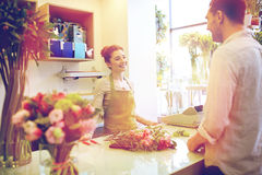 Smiling florist woman and man at flower shop Stock Photos