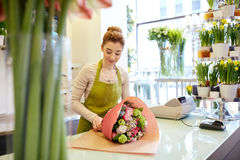 Smiling florist woman packing bunch at flower shop Royalty Free Stock Photos