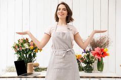 Smiling florist woman standing near table with different flowers. In workshop and looking at camera with hands aside Stock Image