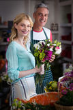Smiling florists holding bunch of flowers in flower shop Stock Image