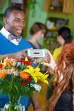 Smiling Flower Shop Customer using Electronic Coupon. Happy customer in a busy flower shop with electronic coupon on his smartphone Stock Photo