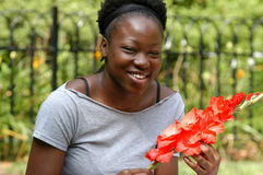 Smiling with flowers. Young african american woman smiles while holding flowers royalty free stock photos