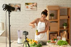 Blogging. Smiling food blogger adding water to glass with ingredients for lemonade royalty free stock photography