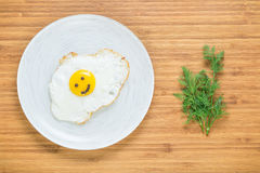 Smiling fried egg lying on a white plate on a wooden cutting board with bunch of dill. Classic Breakfast concept. Royalty Free Stock Photography