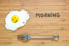 Smiling fried egg lying on a wooden cutting board with morning inscription near it. Classic Breakfast concept. Royalty Free Stock Image