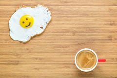 Smiling fried egg lying on a wooden cutting board with small red cup of coffee near it. Classic Breakfast concept. Royalty Free Stock Photos