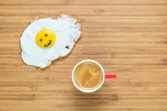 Smiling fried egg lying on a wooden cutting board with small red cup of coffee near it. Classic Breakfast concept. Stock Images