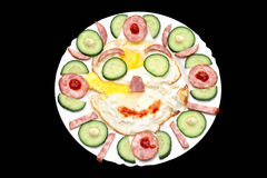Smiling fried eggs. Fried eggs with sausage, a cucumber, mayonnaise and ketchup close up as the smiling face Stock Images