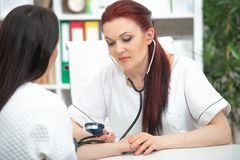 A smiling friendly doctor takes a patient in his office and measures pressure. Woman gives medical advice.  stock photos