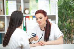 A smiling friendly doctor takes a patient in his office and measures pressure. Woman gives medical advice.  royalty free stock photos
