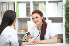 A smiling friendly doctor takes a patient in his office and measures pressure. Woman gives medical advice.  royalty free stock photography