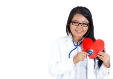 Smiling, friendly female doctor with glasses holding a stethoscope up to a heart Stock Photography
