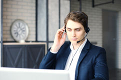 Smiling friendly handsome young male call centre operator. Smiling friendly handsome young male call centre operator Royalty Free Stock Images