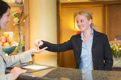 Smiling friendly hotel receptionist. Standing behind the service desk in a hotel lobby booking in a female client handing her the room keys for her stay during Royalty Free Stock Image