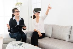 Friendly house agent explaining building design. Smiling friendly house agent explaining building design when her client using VR technology equipment viewing Stock Photo