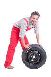 Smiling and friendly mechanic pushing a new tire Stock Images