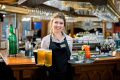 Smiling friendly waitress serving a pint of draft beer in a pub. Portrait of happy young woman serving beer in bar. Looking at camera smiling royalty free stock image