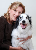 Smiling, friendly woman hugging dog Royalty Free Stock Photography