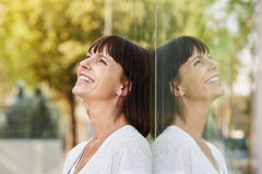 Smiling friendly woman leaning against reflection in building Royalty Free Stock Image