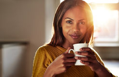 Smiling friendly young black woman drinking coffee Stock Image