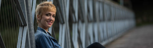 Smiling friendly young blond woman panorama stock photography