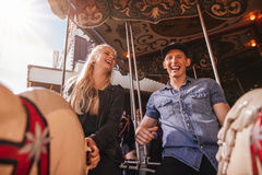 Smiling friends on amusement park carouse Royalty Free Stock Photography