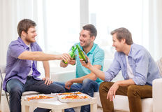 Smiling friends with beer and pizza hanging out Stock Photography