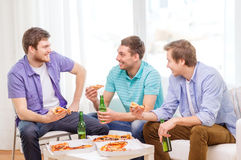 Smiling friends with beer and pizza hanging out Stock Images