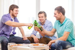 Smiling friends with beer and pizza hanging out Stock Photos