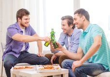 Smiling friends with beer and pizza hanging out Stock Image