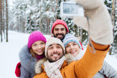 Smiling friends with camera in winter forest Stock Photography