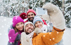 Smiling friends with camera in winter forest Royalty Free Stock Photo