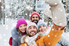 Smiling friends with camera in winter forest Stock Images