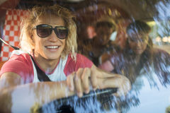 Smiling friends in camper van seen through windshield Stock Photography