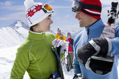 Smiling friends carrying skis Royalty Free Stock Photography