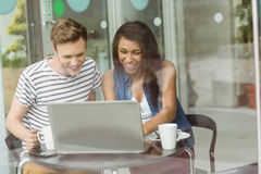 Smiling friends with chocolate cake using laptop Stock Photography