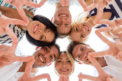 Smiling friends in circle. Friendship, happiness and people concept - smiling friends in circle showing victory sign Stock Photography