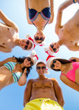 Smiling friends in circle on summer beach. Friendship, christmas, summer vacation, holidays and people concept - group of smiling friends wearing swimwear and Royalty Free Stock Photography