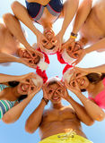 Smiling friends in circle on summer beach. Friendship, christmas, summer vacation, holidays and people concept - group of smiling friends wearing swimwear and Stock Photography