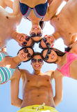 Smiling friends in circle on summer beach. Friendship, happiness, summer vacation, holidays and people concept - group of smiling friends wearing swimwear Stock Photography