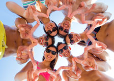 Smiling friends in circle on summer beach. Friendship, happiness, summer vacation, holidays and people concept - group of smiling friends wearing swimwear and Royalty Free Stock Image