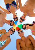 Smiling friends in circle on summer beach. Friendship, happiness, summer vacation, holidays and people concept - group of smiling friends wearing swimwear Royalty Free Stock Images